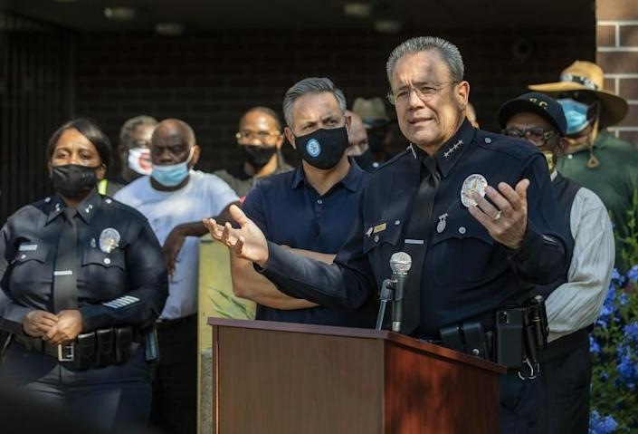 LAPD Police Chief Michel Moore, right, addresses the media outside the Southeast Community Police Station
