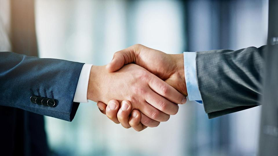 Closeup shot of two businessmen shaking hands in an office.