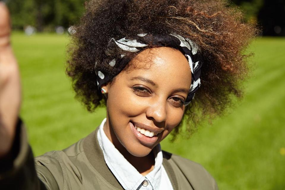 woman with Afro haircut wearing black bandana, taking selfie, holding mobile phone or other device in right hand, smiling and squinting eyes in bright sun