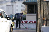 Authorities clean scene after a man rammed a car into two officers at the barricade on Capitol Hill in Washington, Friday, April 2, 2021. (AP Photo/Alex Brandon)