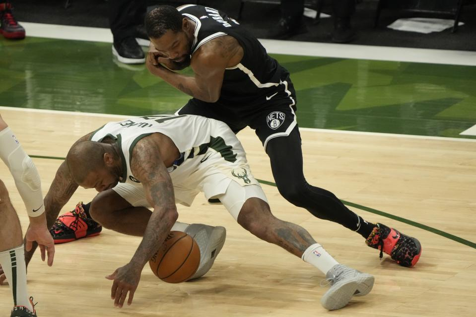 Milwaukee Bucks' P.J. Tucker steals the ball from Brooklyn Nets' Kevin Durant during the first half of Game 4 of the NBA Eastern Conference basketball semifinals game Sunday, June 13, 2021, in Milwaukee. (AP Photo/Morry Gash)