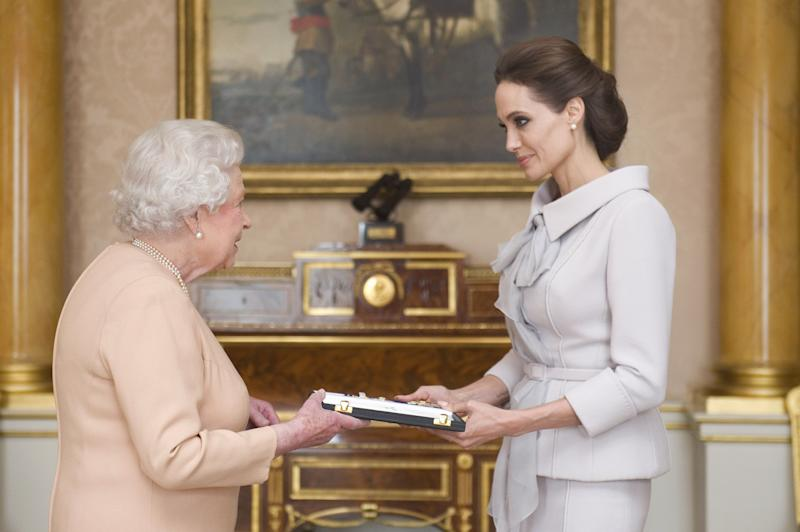 US actress Angelina Jolie (R) is presented with the Insignia of an Honorary Dame Grand Cross of the Most Distinguished Order of St Michael and St George by Britain's Queen Elizabeth II in the 1844 Room at Buckingham Palace in central London, on October 10, 2014. Angelina Jolie was awarded an honorary damehood (DCMG) for services to UK foreign policy and the campaign to end war zone sexual violence. AFP PHOTO/Anthony Devlin/POOL (Photo credit should read Anthony Devlin/AFP via Getty Images)