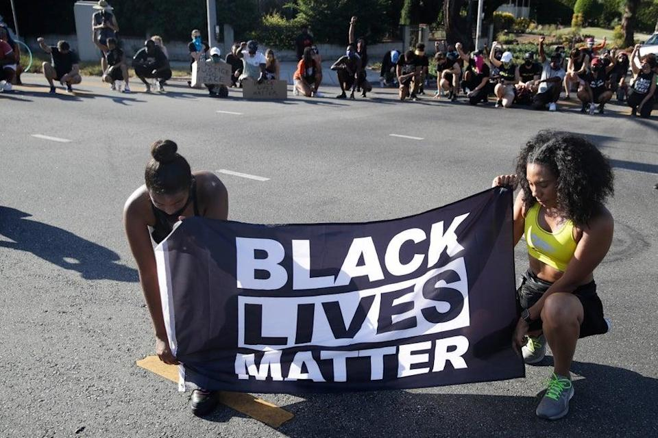 Protesters display a BLM banner (Associated Press)