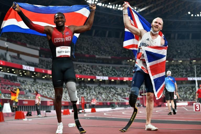 Costa Rica's Sherman Isidro Guity Guity (L) and Britain's Jonnie Peacock (R) celebrate after the men's 100m (T64) athletics final (AFP/Kazuhiro NOGI)