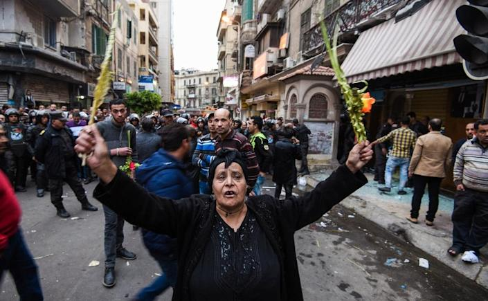 An Egyptian woman raises braided palm leaves, originally intended for Palm Sunday celebrations, during a gathering outside the Coptic Orthodox Patriarchate in Alexandria after a bomb blast struck outside while worshippers attended Palm Sunday mass on April 9, 2017 (AFP Photo/MOHAMED EL-SHAHED)
