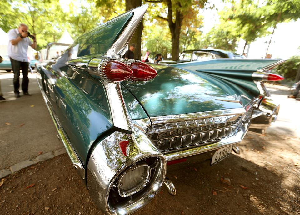 A man takes a picture of a 1959 Cadillac Eldorado Biarritz convertible car during a prologue of the Raid Suisse-Paris 2013 vintage car rally in Zurich August 21, 2013. The Raid Suisse-Paris 2013 runs from August 22 to 25 in Basel. REUTERS/Arnd Wiegmann (SWITZERLAND - Tags: TRANSPORT)