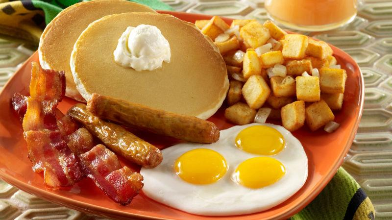 Pancakes, potatoes, bacon, and eggs on an orange plate