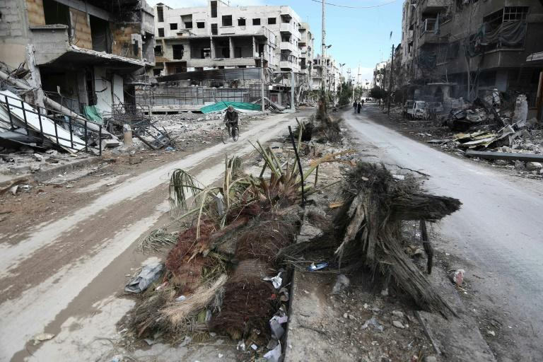 A Syrian man cycles past destroyed buildings in the rebel-held town of Hamouria, in the besieged Eastern Ghouta region on the outskirts of Damascus