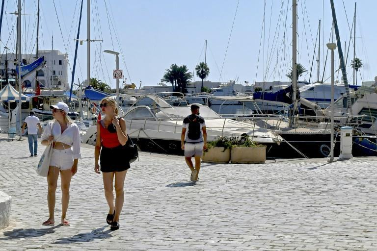 Tourists walk past moored boats at a marina in Tunisia's coastal city of Sousse; despite the crisis, the country remains open to visitors