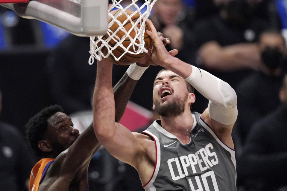Los Angeles Clippers center Ivica Zubac, right, shoots as Phoenix Suns center Deandre Ayton defends during the second half in Game 4 of the NBA basketball Western Conference Finals Saturday, June 26, 2021, in Los Angeles. (AP Photo/Mark J. Terrill)