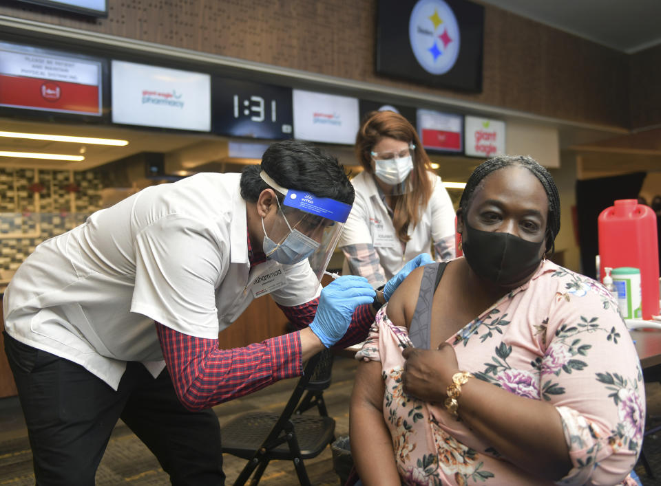 Dena Langston, a Pre-K teacher at the Pittsburgh suburb's Homewood-Brushton YWCA, receives a COVID vaccination from Muhammad Cheema, a pharmacist with Giant Eagle supermarket chain, Thursday, March 11, 2021, at Heinz Field in Pittsburgh. Giant Eagle Pharmacy partnered with the Pittsburgh Public Schools (PPS) to conduct a two-day COVID-19 vaccine clinic at Heinz Field. (Nate Guidry/Pittsburgh Post-Gazette via AP)