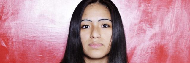 hispanic woman with serious face and long, straight black hair staring at camera with a red background
