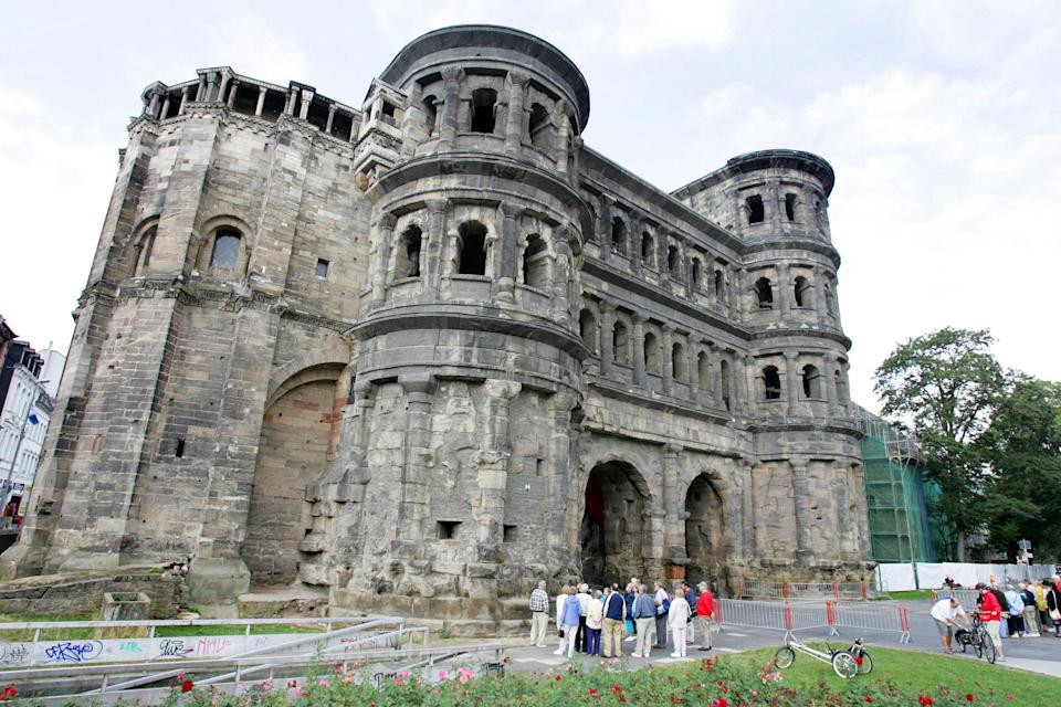 <p>Tourist in front of Trier's most famous monument, the Porta Nigra, or Black Gate</p>AFP via Getty Images