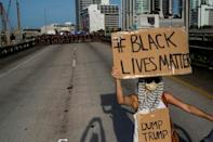 A protestor holding a Black Lives Matter / Dump Trump sign stands in front of a Florida state trooper line during a rally in Miami