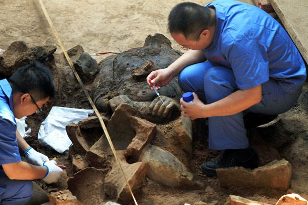 This picture taken on June 9, 2012 shows Chinese archaeologists at work in the extended excavation of the Pit One of the Terracotta Warriors and Horses Museum in Xian, as they measue and record the dimensions of the latest terracotta warrior find in Xian, China's Shaanxi province. Excavations in China have unearthed a stunning new collection of 2,000-year-old terracotta warriors and hundreds of other artefacts, as Chinese archaeologists unveiled 120 new terracotta warriors at the Qin Shihuang Unesco World Heritage site in Shaanxi province.