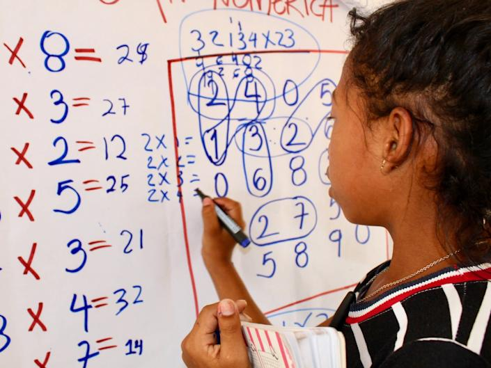 In Colombia, Maria, 8 years-old, from Venezuela, works on maths problems: Jenn Gardella/Save the Children