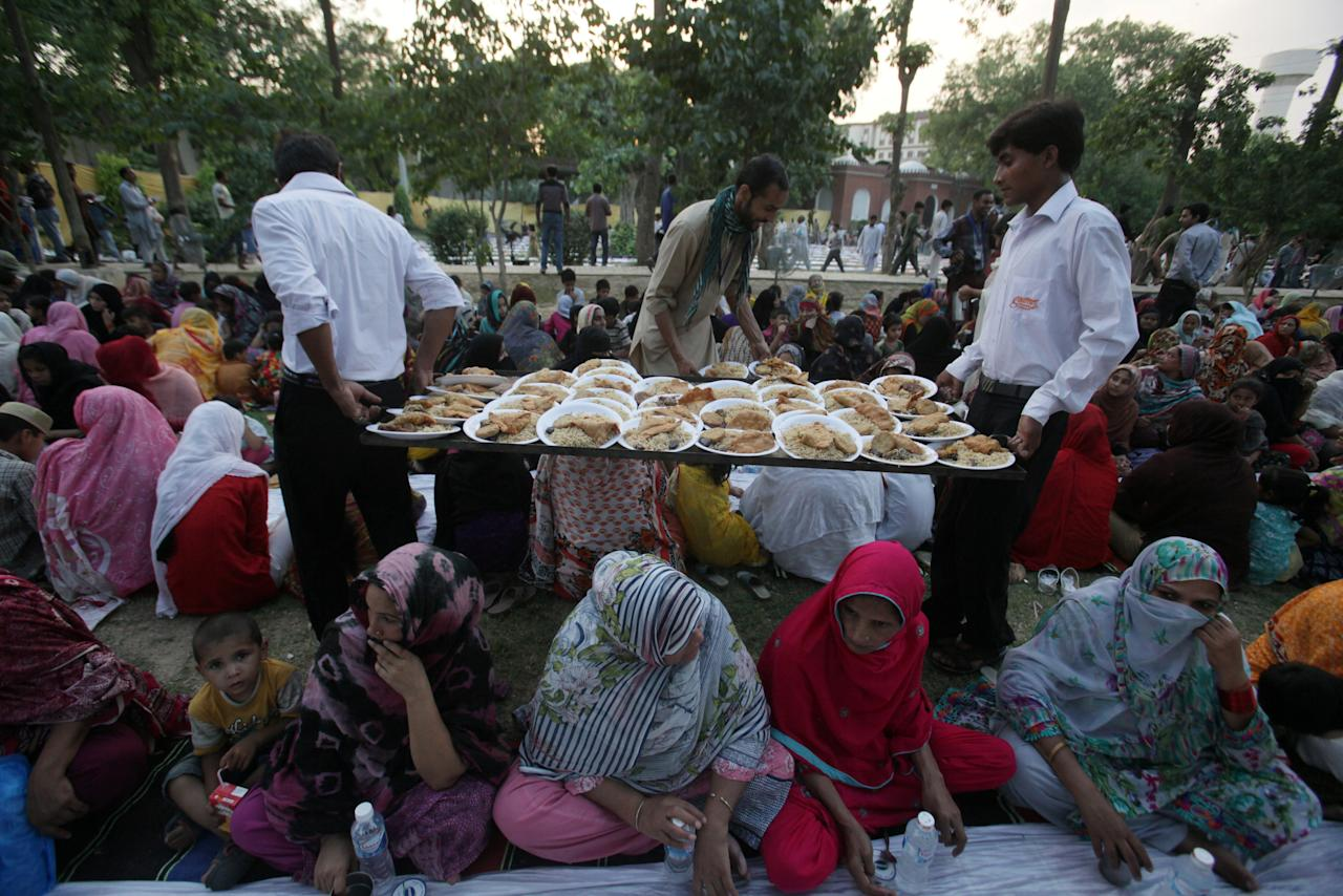 Men serve food as women break fast in a park during the Muslim holy month of Ramadan in Lahore, Pakistan, May 29, 2017. REUTERS/Mohsin Raza
