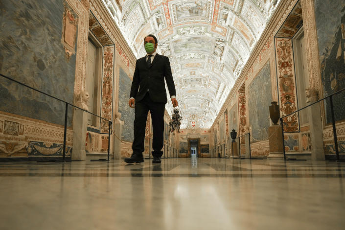 """Gianni Crea, the Vatican Museums chief """"Clavigero"""" key-keeper, holds a bunch of keys as he walks down the """"Maps Aisle"""" to open the museum's rooms and sections, at the Vatican, Monday, Feb. 1, 2021. Crea is the """"clavigero"""" of the Vatican Museums, the chief key-keeper whose job begins each morning at 5 a.m., opening the doors and turning on the lights through 7 kilometers of one of the world's greatest collections of art and antiquities. The Associated Press followed Crea on his rounds the first day the museum reopened to the public, joining him in the underground """"bunker"""" where the 2,797 keys to the Vatican treasures are kept in wall safes overnight. (AP Photo/Andrew Medichini)"""