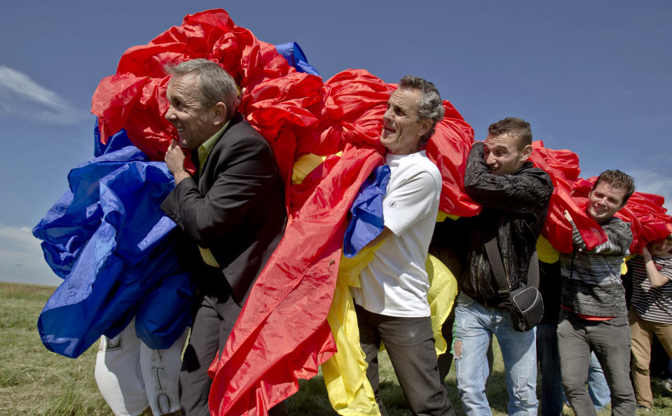 Romanians carry a huge national flag on the Clinceni Airfield, south of Bucharest, Romania, Monday, May 27, 2013. Romania entered the Guinness Book of records after it unveiled the largest flag ever made. It took about 200 people several hours Monday to unfurl a five-ton flag of Romania which organizers said measured 349.4 meters by 226.9 meters, about three times the size of a football pitch.(AP Photo/Vadim Ghirda)