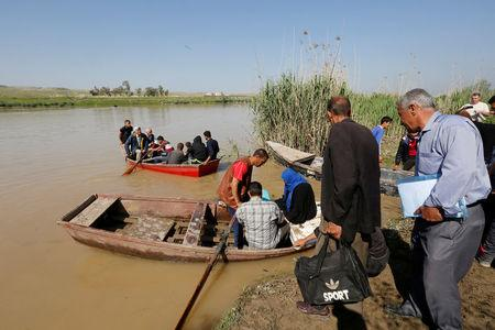Displaced Iraqis from Mosul cross the Tigris by boat as flooding after days of rainfall has closed the city's bridges, at the village of Thibaniya, south of Mosul. REUTERS/Muhammad Hamed