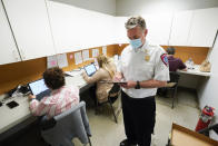"""Sterling Heights Fire Department Chief Kevin Edmond works at a vaccine distribution location in Sterling Heights, Mich., Wednesday, April 28, 2021. While staffing levels in his department have remained the same since the mid-1990s, the number of runs the department makes for various emergencies has increased from 5,000 annually to more than 16,000. """"A lot of people are using EMS as their primary health care providers,"""" often because they have no insurance, Edmond said. (AP Photo/Paul Sancya)"""