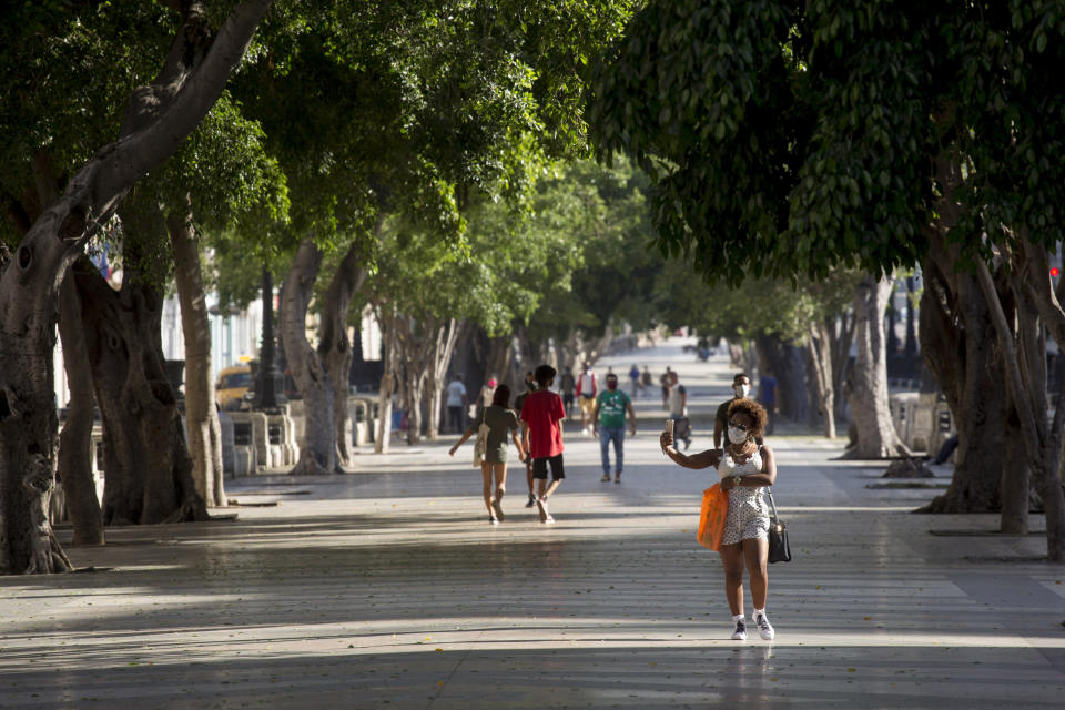 People walk through Paseo del Prado in Havana, Cuba, Monday, July 12, 2021, the day after protests against food shortages and high prices amid the coronavirus crisis. (AP Photo/Ismael Francisco)