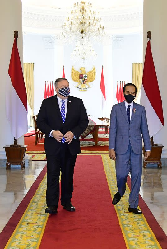 U.S. Secretary of State Mike Pompeo and Indonesian President Joko Widodo wearing protective masks walk during their meeting at the Presidential Palace in Bogor