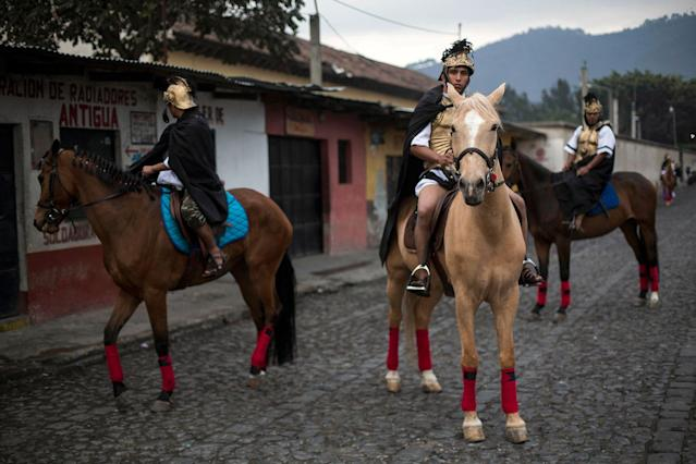 <p>Devotees dressed as Roman soldiers wait on horseback to join the Jesus of Nazareth Good Friday procession in Antigua, Guatemala, Friday, March 30, 2018. Residents of Antigua turn their town into a biblical Jerusalem complete with Roman soldiers on horseback and trumpets marking the coming of Christ. (Photo: Moises Castillo/AP) </p>