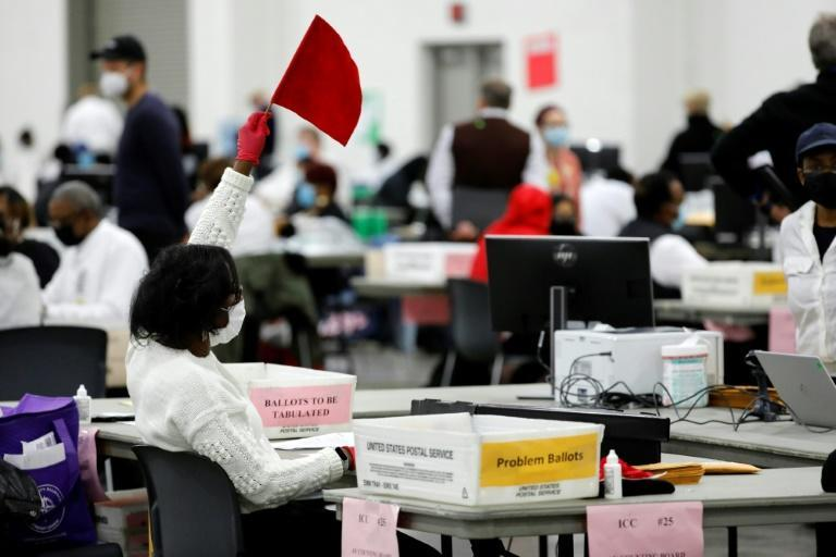 An election worker seeks assistance while counting absentee ballots in Detroit, Michigan