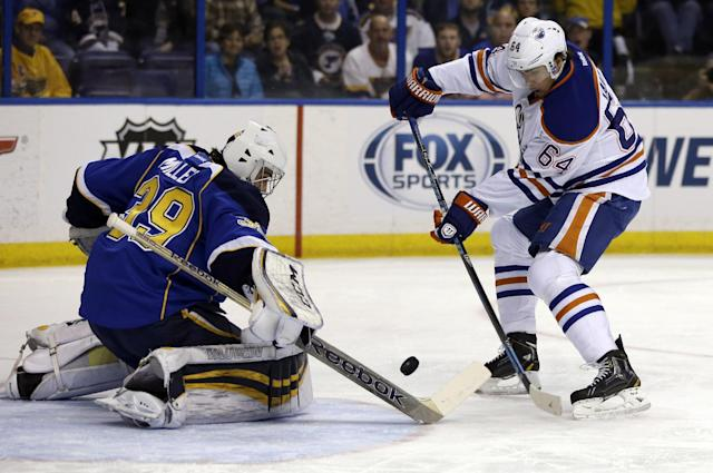 St. Louis Blues goalie Ryan Miller, left, deflects a shot from Edmonton Oilers' Nail Yakupov, of Russia, during the first period of an NHL hockey game, Thursday, March 13, 2014, in St. Louis. (AP Photo/Jeff Roberson)