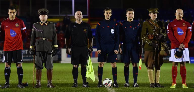 """Bundeswehr football captain Alexander Hess (L), Swiss referee Stephan Klossner (3L) and British Army football captain Keith Emmerson (R) stand on the pitch alongside people in military WWI uniforms at the start of the """"Game of Truce"""" (AFP Photo/Ben Stansall )"""