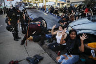 FILE - In this May 31, 2020, file photo, protesters raise their hands on command from police as they are detained prior to arrest and processing at a gas station on South Washington Street in Minneapolis. The federal government deliberately targeted Black Lives Matter protesters via heavy-handed criminal prosecutions in an attempt to disrupt and discourage the global movement that swept the nation last summer in the wake of the police killing of George Floyd, according to a new report released Wednesday, Aug. 18, 2021, by The Movement for Black Lives. (AP Photo/John Minchillo, File)