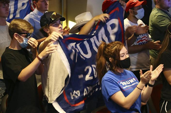 Young people, some of whom are masked, hold up a campaign banner bearing the word Trump
