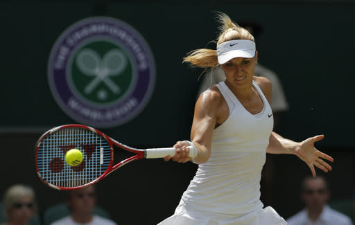 Sabine Lisicki of Germany plays a return to Simona Halep of Romania during their women's singles quarterfinal match at the All England Lawn Tennis Championships in Wimbledon, London, Wednesday, July 2, 2014. (AP Photo/Pavel Golovkin)