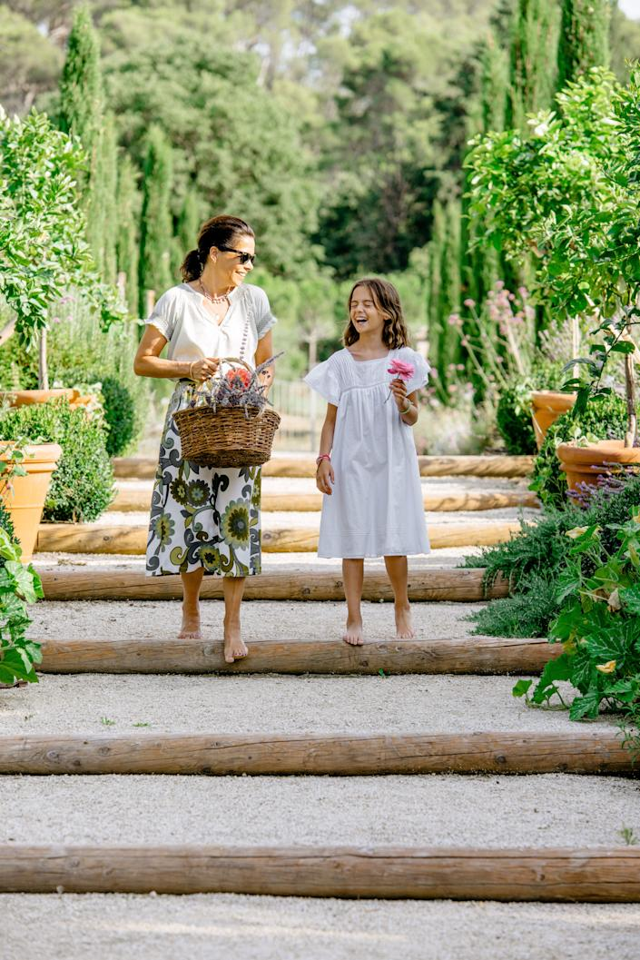 "<div class=""caption""> Douzal strolls the grounds with her nine-year-old daughter, Athina, carrying cut flowers planted with help of Benoit Hochart of <a href=""https://www.facebook.com/pages/category/Home-Decor/Roseraie-de-Chateaubois-Benoit-Hochart-101102128290801/"" rel=""nofollow noopener"" target=""_blank"" data-ylk=""slk:Roseraie de Chateaubois"" class=""link rapid-noclick-resp"">Roseraie de Chateaubois</a>, famous for his roses. </div>"