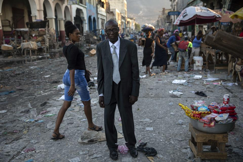 Monon, 54, walks in downtown Port-au-Prince, Haiti, returning to his home after the funeral of his son at the general cemetery, late afternoon, Tuesday, Sept. 21, 2021. (AP Photo/Rodrigo Abd)