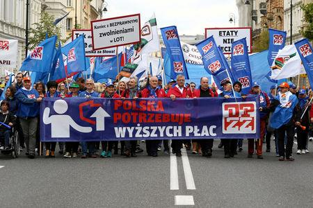 """People take part in an anti-government demonstration of public-sector trade unions demanding higher wages in Warsaw, Poland September 22, 2018. The banner reads, """"Poland needs higher wages."""" Agencja Gazeta/Slawomir Kaminski via REUTERS"""
