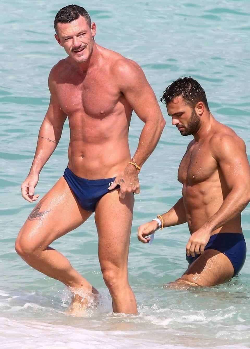 <p>Luke Evans enjoys a beach day with a friend on Tuesday in Miami.</p>