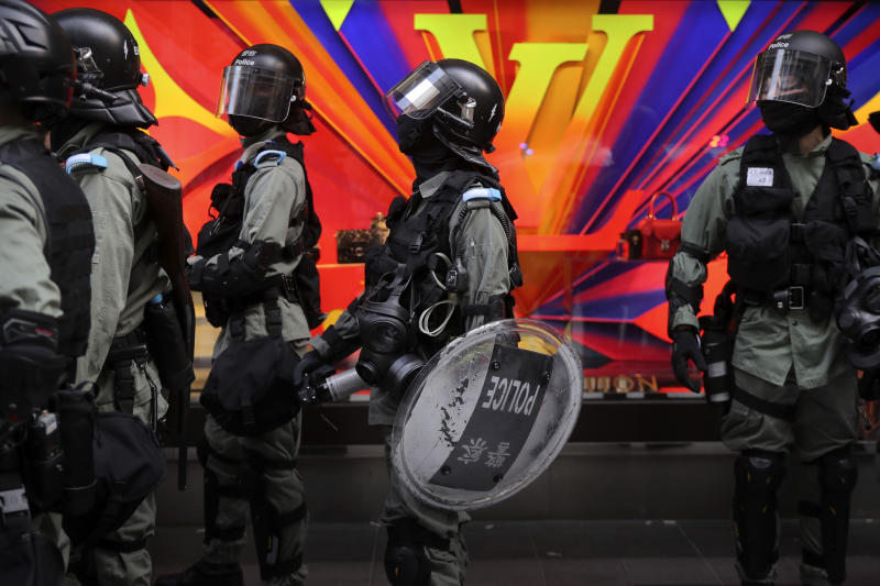 Riot police gather near a Louis Vuitton store during a demonstration in the financial district in Hong Kong, Wednesday, Nov. 20, 2019. Hong Kong schools reopened Wednesday after a six-day shutdown but students and commuters faced transit disruptions as the last protesters remained holed up on a university campus. (AP Photo/Kin Cheung)