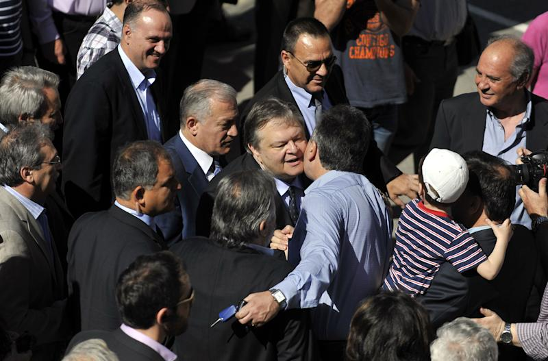 Leader of the Greek Socialist PASOK party Evangelos Venizelos, center, is greeted by supporters upon his arrival outside a polling station in Thessaloniki, northern Greece Sunday May 6, 2012. Greeks cast ballots on Sunday in their most critical _ and uncertain _ election in decades, with voters set to punish the two main parties that are being held responsible for the country's dire economic straits. (AP Photo/Nikolas Giakoumidis)