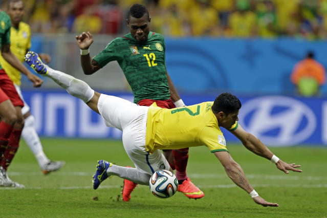 Brazil's Hulk, front, falls in front of Cameroon's Henri Bedimo during the group A World Cup soccer match between Cameroon and Brazil at the Estadio Nacional in Brasilia, Brazil, Monday, June 23, 2014. (AP Photo/Andre Penner)