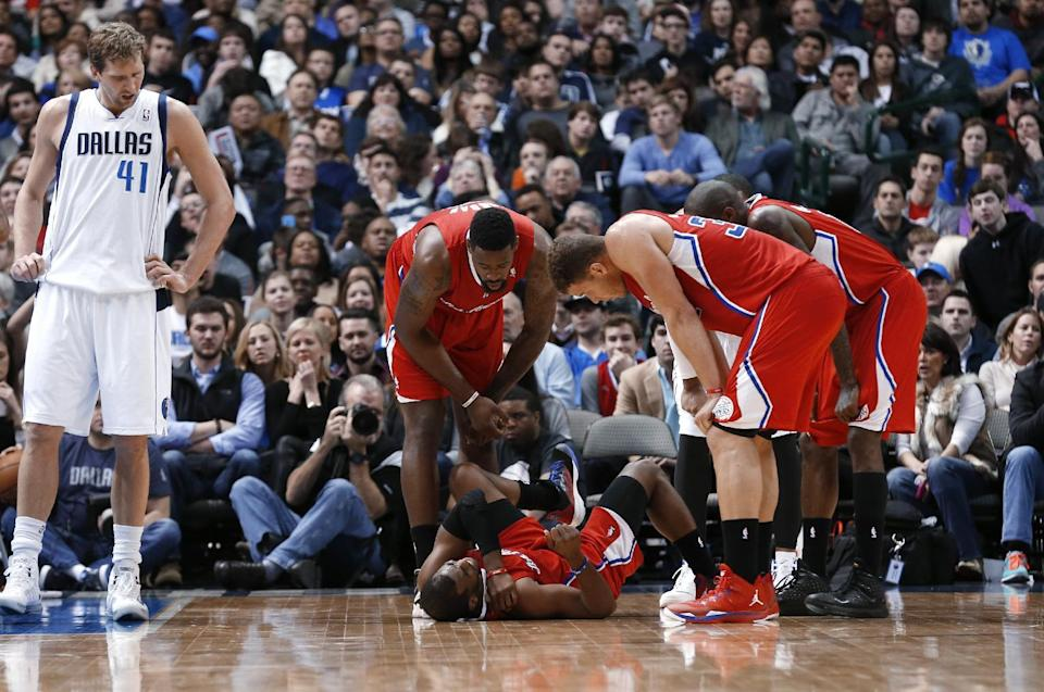 Dallas Mavericks forward Dirk Nowitzki (41) stands nearby as Los Angeles Clippers guard Chris Paul (3) is checked on my teammates, including center DeAndre Jordan, left, and forward Blake Griffin (32), after he was injured during the second half of an NBA basketball game Friday, Jan. 3, 2014, in Dallas. The Clippers won 119-112. (AP Photo/Sharon Ellman)