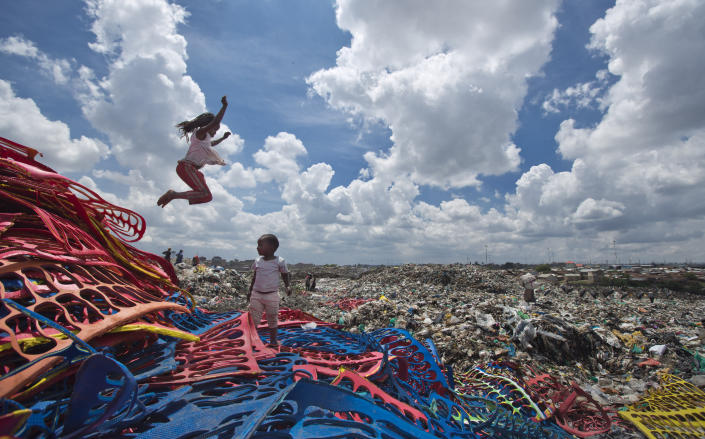 FILE - In this Thursday, Nov. 12, 2015 file photo, Joyce Njeri, 8, enjoys a rare moment of fun playing like a child with Shantel Akinyi, 2, on a pile of discarded sheets of plastic left over from the manufacture of flip-flops, at the garbage dump where Joyce herself and the mother of Shantel both work, in the Dandora slum of Nairobi, Kenya, before a ban on plastic bags came into force in Kenya in 2017. The oil industry in 2020 has asked the United States to pressure Kenya to change its world-leading stance against the plastic waste that litters Africa, according to environmentalists who fear the continent will be used as a dumping ground. (AP Photo/Ben Curtis, File)
