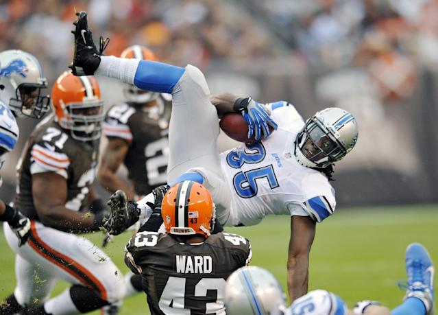 Detroit Lions running back Joique Bell (35) is tripped up by Cleveland Browns strong safety T.J. Ward (43) after an 8-yard gain in the first quarter of an NFL football game Sunday, Oct. 13, 2013 in Cleveland. (AP Photo/David Richard)