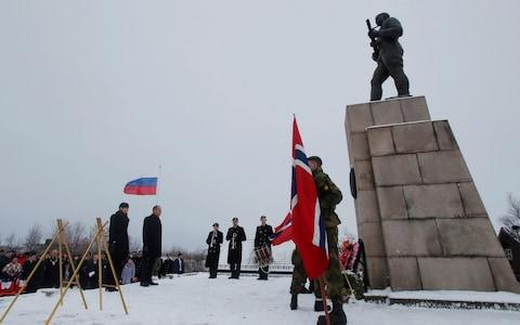<span>Norway and Russia's foreign ministers pay their respects on Friday at a memorial to the Soviet soldiers who liberated Kirkenes from the Nazis</span> <span>Credit: Maxim Shemetov/Reuters </span>