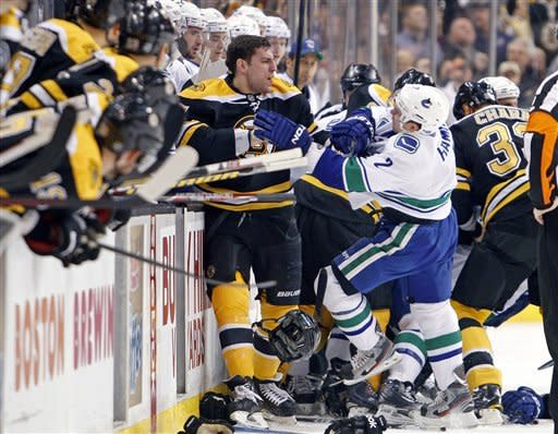 Boston Bruins' Milan Lucic, center left, and Vancouver Canucks' Dan Hamhuis (2) and other members from both teams fight in front of the benches during the first period of an NHL hockey game in Boston, Saturday, Jan. 7, 2012. (AP Photo/Michael Dwyer)