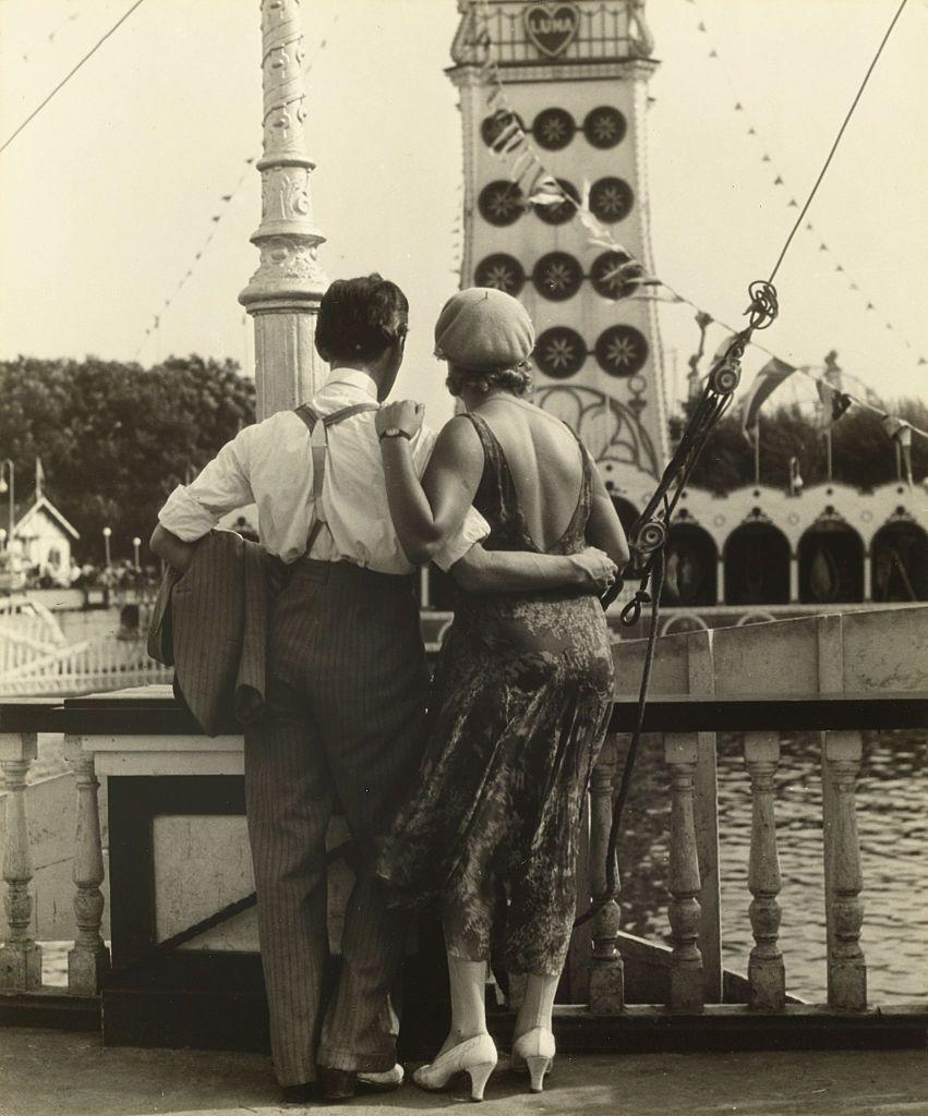 <p>A couple takes a stroll through the fairgrounds at Coney Island. </p>