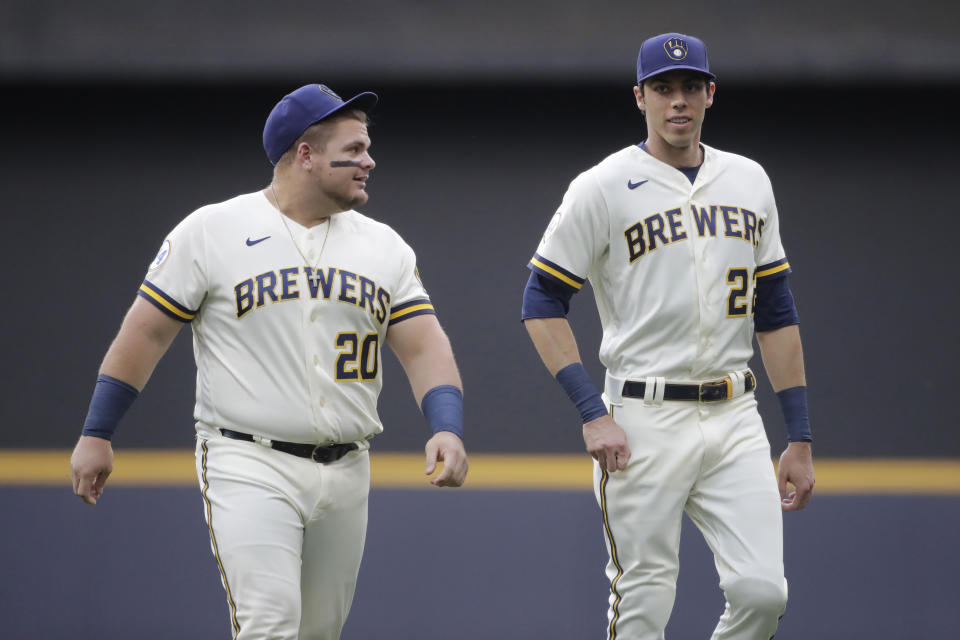 Milwaukee Brewers' Christian Yelich (22) and Daniel Vogelbach (20) warm up before a baseball game against the Cincinnati Reds Monday, June 14, 2021, in Milwaukee. (AP Photo/Aaron Gash)