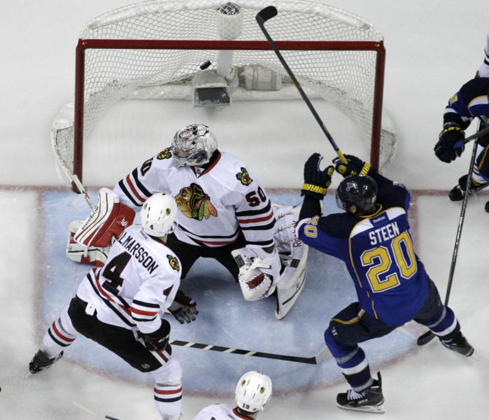 St. Louis Blues' Alexander Steen (20) scores the game-winning goal past Chicago Blackhawks goalie Corey Crawford and Niklas Hjalmarsson (4) during the third overtime in Game 1 of a first-round NHL hockey Stanley Cup playoff series Thursday, April 17, 2014, in St. Louis. The Blues won 4-3 in triple overtime. (AP Photo/Jeff Roberson)