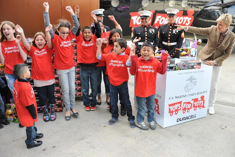 """Ellen DeGeneres, far right, with U.S. Marines and her helpers attend the Ellen DeGeneres officially launches the Duracell """"Power a Smile"""" Program, on Friday, Nov. 22, 2013, at Van Nuys Airport in Los Angeles. (Photo by Richard Shotwell/Invision/AP)"""
